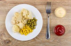 Cauliflower, sweet corn, green peas in plate and fork Stock Photo
