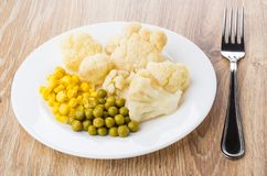 Cauliflower, sweet corn, green peas in plate and fork Royalty Free Stock Photography