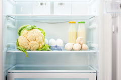 Cauliflower, white eggs, champignon mushrooms and two glass bottles of yoghurt on shelf of open empty refrigerator Royalty Free Stock Photos