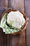 Cauliflower in woven basket on wooden background Royalty Free Stock Images