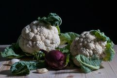 Cauliflowers, onion and garlic on a wooden table. Low key still life with cauliflowers, onion and garlic on a wooden table Stock Images