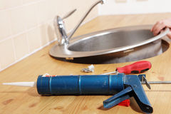 Caulking gun. With silicone sealant against kitchen sink installation process Stock Photography