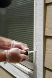 Caulking Holes in Window Frame. Vinyl gloved hands with tube of white caulking filling holes that developed in a home outdoor window frame Stock Photography