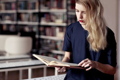 Causasian blonde woman reading a book in a public library. Red lips, long white hair Stock Photos
