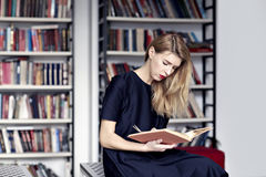 Causasian blonde woman reading a book in a public library. Red lips, long white hair Royalty Free Stock Photography