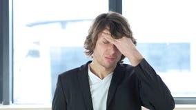 Cause dor na cabeça, homem irritado virado com dor de cabeça em seu escritório imagens de stock