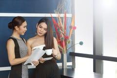 Causerie asiatique de femme d'amis intimes la belle au sujet de drôle pensent Photographie stock libre de droits