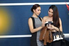 Causerie asiatique de femme d'amis intimes la belle au sujet de drôle pensent Photo stock