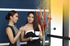 Causerie asiatique de femme d'amis intimes la belle au sujet de drôle pensent Photos stock