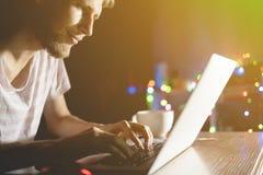 Causerie de jeune homme dans le réseau social avec des amis à l'aide du téléphone et de l'ordinateur portable tard pendant la nui photo stock