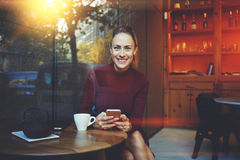 Causerie femelle gaie magnifique avec ses amis par l'intermédiaire de téléphone de cellules pendant le repos en café confortable Image stock