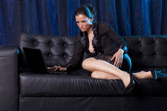 Causerie sexy - femme attirante à l'aide de l'ordinateur portable Photographie stock libre de droits
