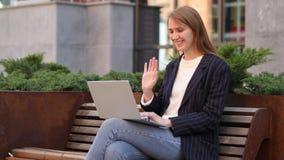 Causerie visuelle de Web sur l'ordinateur portable tout en se reposant sur le banc en dehors du bureau image libre de droits