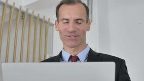 Causerie visuelle en ligne par l'homme d'affaires ?g? par milieu banque de vidéos