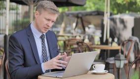 Causerie visuelle en ligne par l'homme d'affaires Sitting en café extérieur banque de vidéos