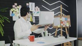 Causerie visuelle en ligne par l'homme s'asseyant au bureau clips vidéos