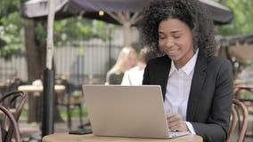 Causerie visuelle en ligne par la femme d'affaires africaine Sitting en café extérieur banque de vidéos