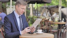 Causerie visuelle en ligne sur la Tablette par l'homme d'affaires, s'asseyant en café extérieur clips vidéos