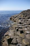 Causeway Coast. Basalt columns making up the Giant's Causeway in Northern Ireland, running down to the sea Royalty Free Stock Photography