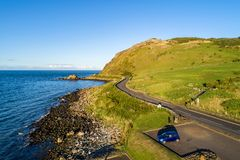 Causeway Coastal Route in Northern Ireland, UK. Northern Ireland, UK. Causeway Coastal Route a.k.a Antrim Coast Road near Ballygalley Head and resort and a car royalty free stock images
