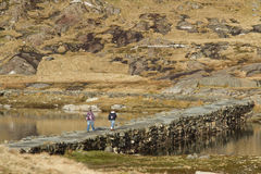 Causeway walkers. Two walkers cross a stone built causeway, with a footpath, between two bodies of water Royalty Free Stock Photo