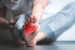 Man with pain in foot. Causian man holds hands to his painful feet, pain in foot. red color is area of pain royalty free stock image