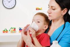 Causian weinig jongen die inhalatie met verstuiver maken bij het ziekenhuis stock afbeelding
