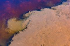 Caustic toxic emissions brown, purple into the pond, bright contrasting spots on the water. The spread of poison in the ecosystem. The concept of pollution of stock photography