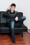 Causual十几岁的男孩坐长沙发谈话在他的手机 免版税图库摄影