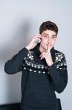 Causual-Teenager, der auf seinem Handy und Zum Schweigen bringen spricht Stockbild