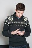 Causual tonårs- pojke som ser hans mobiltelefon Arkivbild