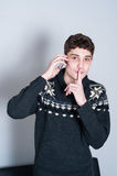 Causual tonårs- pojke som talar på hans mobiltelefon och hyssja ner Fotografering för Bildbyråer
