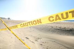 Caution. Sign is set up on the yellow sandy beach Royalty Free Stock Photos