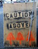 Caution Above Streets Sign. On sidewalk Royalty Free Stock Photo