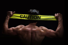 Caution. Attractive young man flexes his muscles whilst holding a caution tape behind his head. Low key portrait on black background Stock Images