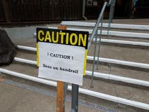 Caution bees on handrail sign on steps. Or stairs royalty free stock photo