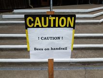 Caution bees on handrail sign on steps. Or stairs royalty free stock image