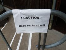 Caution bees on handrail sign on steps. Or stairs royalty free stock photos