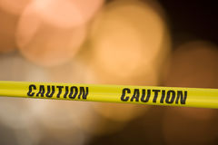 Caution caution. Yellow tape with the word caution on it across a warning light background royalty free stock photo