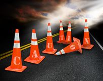Caution cones. Orange construction cones on an asphalt road spelling caution Stock Photos