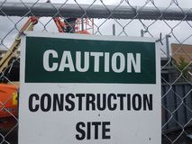Caution construction site sign on metal fence. Caution construction site sign on metal chain link fence stock photography