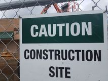 Caution construction site sign on metal fence. Caution construction site sign on metal chain link fence stock image