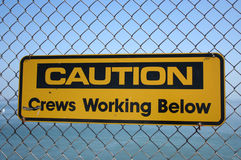 Caution crews working below. Sign on bridge Royalty Free Stock Photo