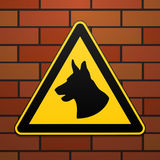 Caution - danger Be aware of dogs The area is guarded by dogs. Warning sign safety. The sign on the brick wall. Vector Stock Photos