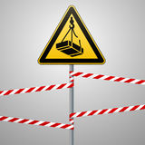 Caution - danger May fall from the height of the load. Safety sign. The triangular sign on a metal pole with warning bands. Light Stock Images