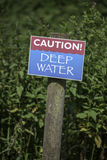 Caution! Deep Water. Ominous sign warning of danger ahead stock image
