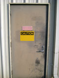 Caution Door. A worn metal door with a blank caution sign on it Royalty Free Stock Image