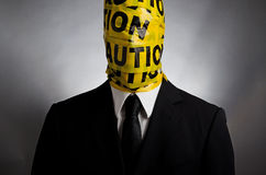 Caution Face. Image of a suit - wearing man with caution tape around his face Stock Photo