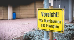 Caution! in front of roof avalanches and icicles in German. On a yellow sign in front of a building stock image