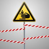 Caution, hands may be injured. Attention is dangerous. Warning sign safety. A yellow triangle with a black image. The. Sign on the pole and protecting ribbons stock illustration